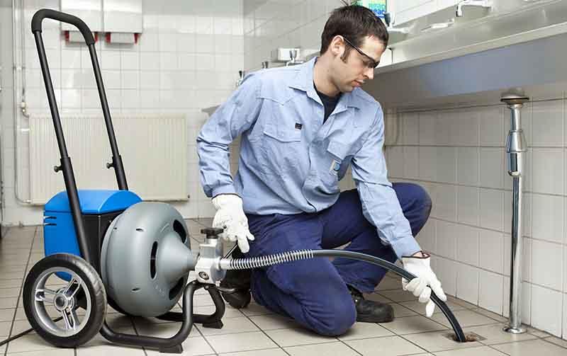plombier qui débouche une canalisation
