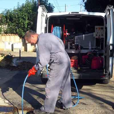 plombier qui débouche une canalisation avec une hydrocureuse