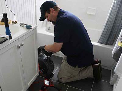 Le plombier inspecte la cnalisation de la baignoire par caméra d'inspection